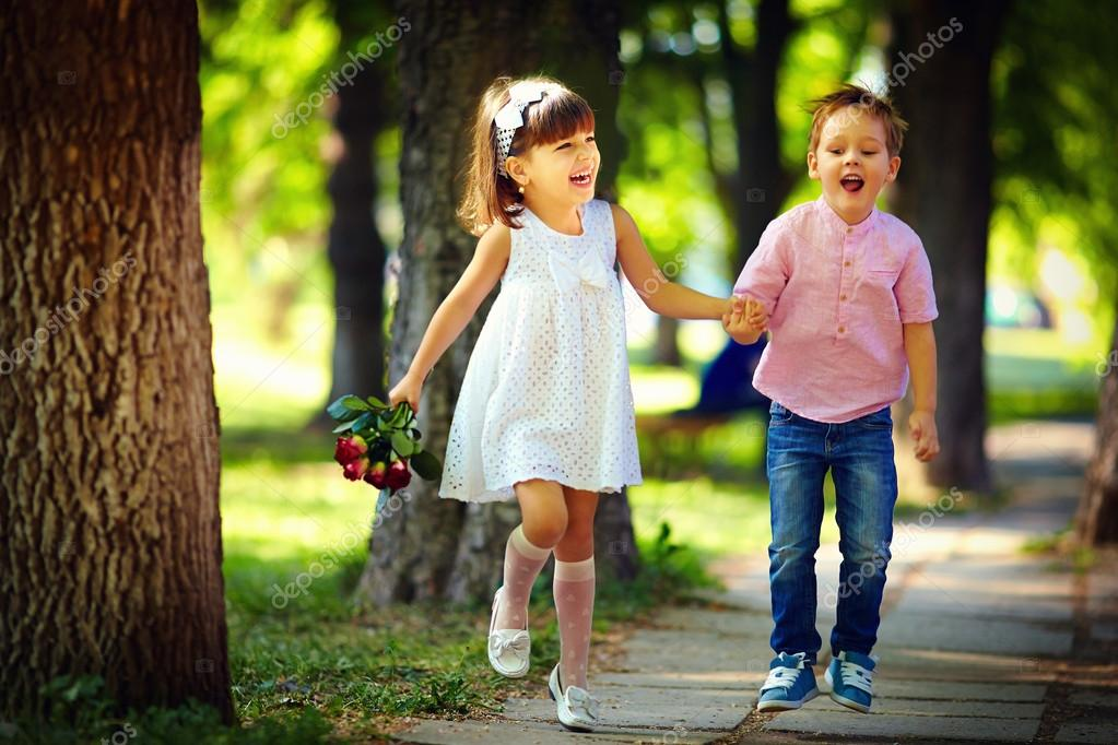 Cute Kids Walking Together In Summer Park Stock Photo