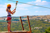 Young woman are ready to descend on zipline in mountain, extreme sport — Stock Photo