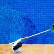 Woman, personnel cleaning the pool from leaves — Stock Photo #75381595