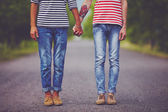 Young male couple holding hands standing on their way together — Stock Photo