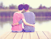 Male couple in love, sitting on wooden pier at riverbank — Стоковое фото