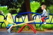 Cute kids having fun on seesaw at playground — 图库照片