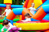 Happy kids, having fun on inflatable attraction playground — Stock Photo