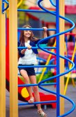 Pretty kid, girl climbs on the stile at playground — Zdjęcie stockowe