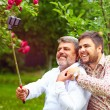 Like father like son. family makes selfie on smartphone — Stock Photo #76381145
