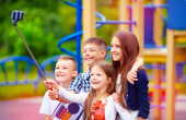 Group of happy friends taking selfy on smart phone, outdoor playground — ストック写真