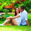 Happy young couple in love sitting near pond with flamingo — Stock Photo #79895598