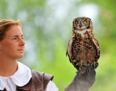 Female falconer holds a gyrfalcon — Stock Photo