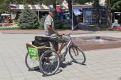 "Street sweeper on a tricycle with a name sign ""We are for clean city!"" on the embankment Gelendzhik, Krasnodar Region, Russia — Stock Photo"