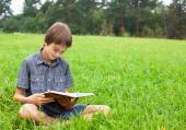 Child reading book outdoor — Stock Photo