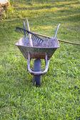 Wheelbarrow with rake on top — Stockfoto