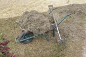 Wheelbarrow full with dry hay and pitchfork leaned on — Stock Photo