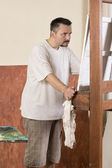 Vertical image of painter while observe a detail on canvas — Stock Photo