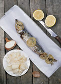 Vertical image of one baked mackerel fish on white paper — Stock Photo