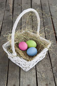 Painted eggs on hay in white basket on wood — Stok fotoğraf
