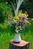 Bouquet of summer flowers on a tree stump — Stockfoto