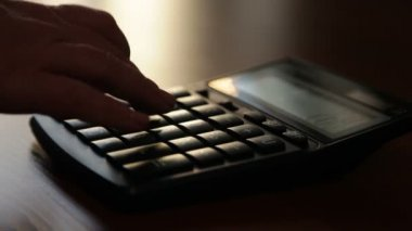 Silhouette of female hand typing numbers on the keypad calculator — Stockvideo