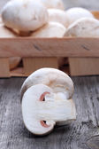 Champignons in a wooden box on old table — Stock Photo