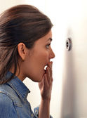 Woman looking out through peephole — Stock Photo