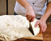 Cook preparing and cutting bread — Stock Photo
