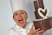 Woman holding a big chocolate cake. — Stock Photo