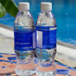Two bottles of transparent water stand on a little table from a mosaic — Stock Photo #57689169