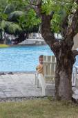 The boy on a chaise lounge near the pool — Stock Photo