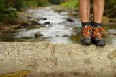 Hiking shoes legs on trunk on mountain trail. — Stock Photo