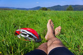 Cyclist relax on grass in mountains. — Stock Photo