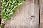 Fresh bunch of rosemary on wooden table. — Stock Photo