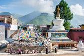 YUSHU(JYEKUNDO), CHINA - Jul 13 2014: Tibetan pilgrims circle the Pagoda. Devotees walk 3 times around the Pagoda and Mani stone to accumulate karma (religious merit). — Stock Photo