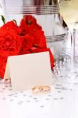 Two golden wedding rings with card, champagne glasses — Stock Photo