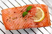 Marinated salmon fillet with lemon on grill — Stock Photo
