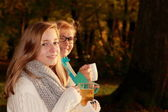 Daughter and mother drink tea in autumn park — Stock Photo