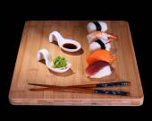 Five species of fish sushi on bamboo board — Stock Photo