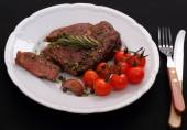 Rib eye steak, garlic, cherry tomatoes, herbs on black — Stock Photo