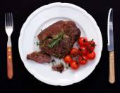 Rib eye steak with cherry tomatoes, garlic, rosemary — Stock Photo