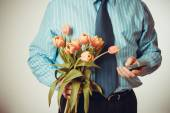 Businessman dials phone number, holding tulips — Stock Photo