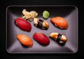 Tuna, salmon and eel sushi on black plate — Stock Photo