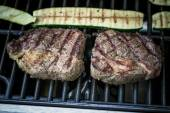 Two rib eye steak with zucchini on grill — Stock Photo