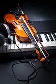 Violin, piano keys and headphones — Stock Photo