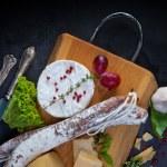 Various cheeses and salami — Stock Photo #67223979