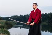Człowiek w mundurze japońskie odzież etniczne samuraj z mieczem katana — Zdjęcie stockowe