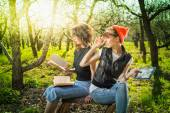 Woman in park outdoor with tablet and book deciding what to use — Stock Photo