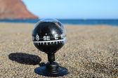 Tourisme la boussole dans le sable — Photo