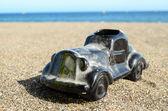 Coche de juguete en la orilla del mar — Foto de Stock