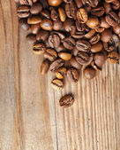 Coffee beans on grunge wooden surface — Stock Photo