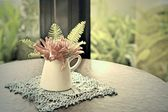 Artificial flowers on the table — Stock Photo