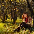Young woman with long red hair reading under the tree — Stock Photo #55712629