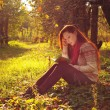 Young woman with long red hair reading under the tree — Stock Photo #55712631